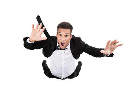 Scared jonge zakenman in dalende positie. vliegende zakenman op een witte achtergrond en huilen