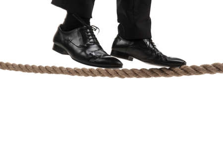 steadiness: businessman walking on tightrope on white background. businessman trying to keep his balance isolated on white background