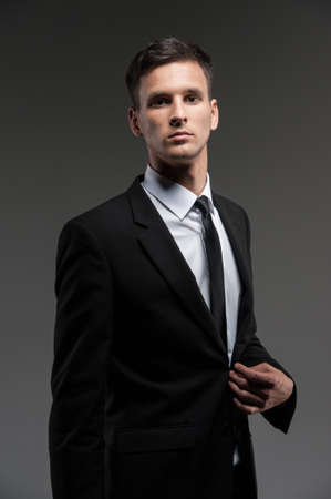 looking into camera: Handsome young man on grey background. side view of man in black suit looking into camera