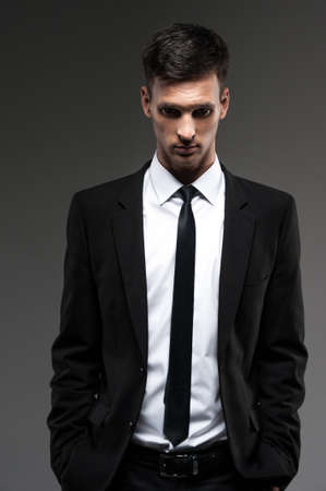 looking into camera: Handsome young man on grey background. front view of man in unbuttoned suit looking into camera  Stock Photo