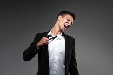 Man loosing tie on grey background. businessman in suit loosening up his tie and expressing emotions Standard-Bild
