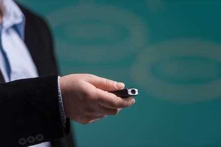 사람 손 레이저 포인팅을 들고. 녹색 배경에 레이저 포인터와 함께 서있는 남자.