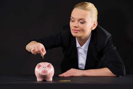 Pink piggy bank standing on dark table. closeup of woman putting coin inside piggy bank photo