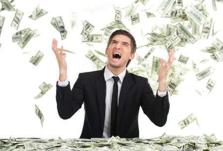 Business man throwing dollar bills and yelling. Young businessman sitting with money in office photo