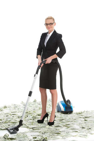 Attractive female businesswoman with vacuum cleaner. Young woman in suit vacuuming money photo