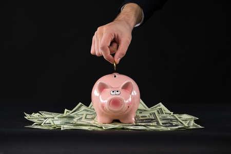 Pink piggy bank standing on dollars. closeup of hand putting coin inside piggy bank photo