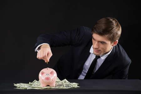 Pink piggy bank standing on dollars. closeup of man putting coin inside piggy bank photo