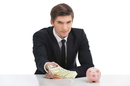 Business man holding dollar bills, isolated on white. Young businessman holding dollars in office
