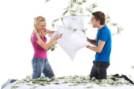 joking: Couple fighting together with pillows in bed. Portrait of happy loving couple with money in bed