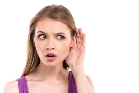 interested: Woman listening with her hand on an ear isolated over white background. happy interested young woman listening to something Stock Photo