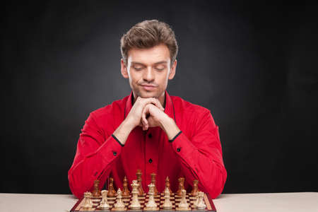 pawn adult: Young casual man sitting over chess. man thinking about move over black