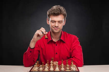 pawn adult: Young casual man sitting over chess. man holding chess piece over black