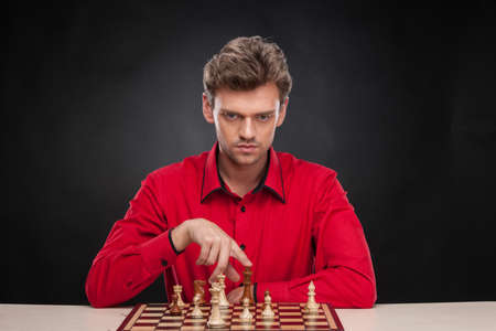 pawn adult: Young casual man sitting over chess. man thinking about next move and touching piece
