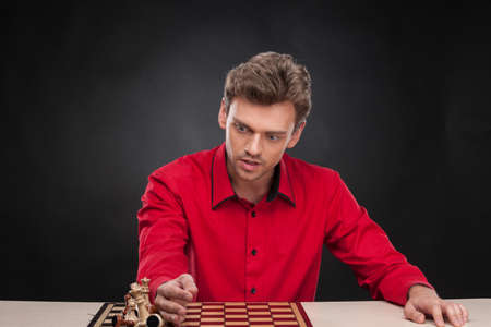 pawn adult: Young casual man sitting over chess. man lost the game and wiping pieces from board