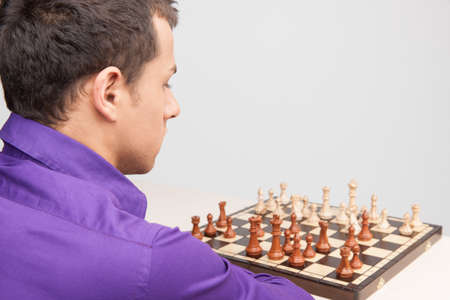 Man playing chess on white background. over shoulder view of young man thinking photo