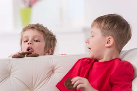 2 years old: Portrait of two kids eating in white sofa. Little boy holding sweets and looking