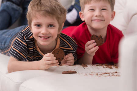 children breakfast: two cute boys lying on couch. two friends eating cookies and smiling Stock Photo