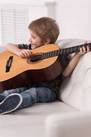 10 fingers: Smiling caucasian boy is playing the acoustic guitar. boy sitting and smiling on couch on white background