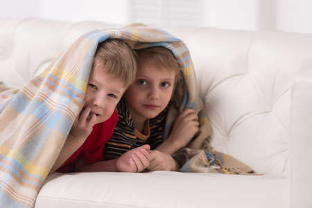 coverlet: Two children looking into camera under blanket. two friends hiding under coverlet and smiling Stock Photo