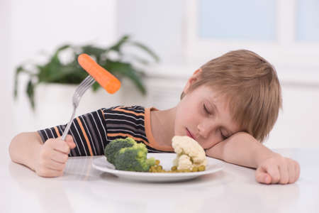 little blond boy eating at kitchen. child holding fork with carrot and sleeping