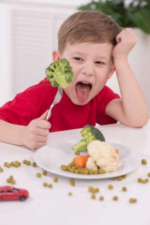 brocoli: niño rubio come en la cocina. niño infeliz sentado en el desayuno y mirando el brócoli