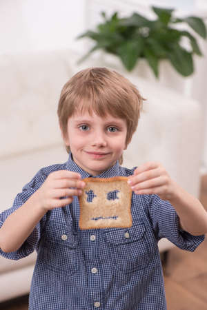 Portrait view of child boy sitting at home. blond boy showing bread at breakfast photo