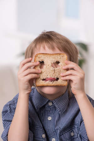 gratified: portrait of funny boy playing with bread. boy holding bread with holes and showing tongue