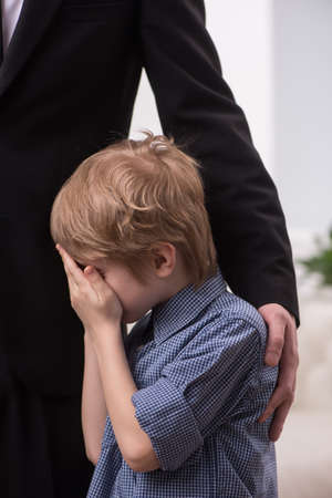 comforted: tall man hugging crying boy. Young boy being comforted by his father Stock Photo