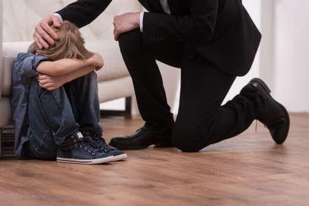 crying boy: Padre de rodillas y comodidades niño triste. niño sentado en el piso en el dormitorio y el llanto