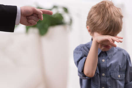 Strict father discipline naughty son. Isolated on white background boy wiping tears Standard-Bild