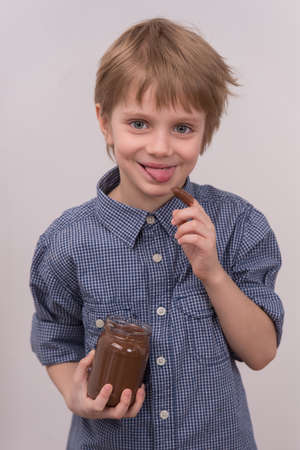 Child licks chocolate glaze with finger. nice boy holding jar and eating chocolate