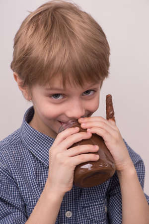Child licks chocolate glaze from jar. nice boy holding jar and eating chocolate