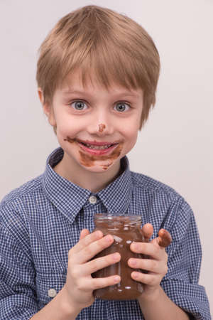 cikolata: Smiling kid eating chocolate from jar. Smeared stained with chocolate lips on white Stock Photo