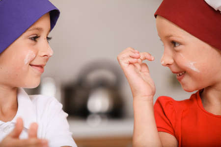closeup of children making cakes and smiling. two kids having fun at kitchen table  photo