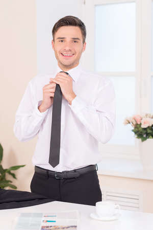 waist up: Close-up of businessman adjusting neck tie. waist up of handsome guy putting on neck tie