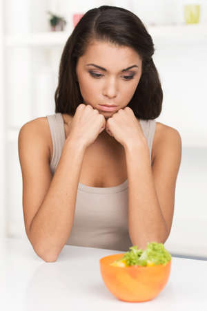 bawl: upset young woman keeping diet and eating vegetables. Sad woman in front of her small diet meal