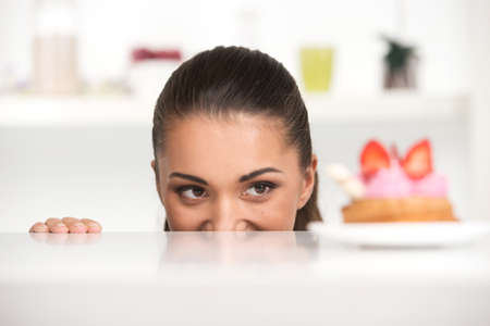 stress testing: Funny girl hiding behind table. woman hiding behind white table and looking at cake
