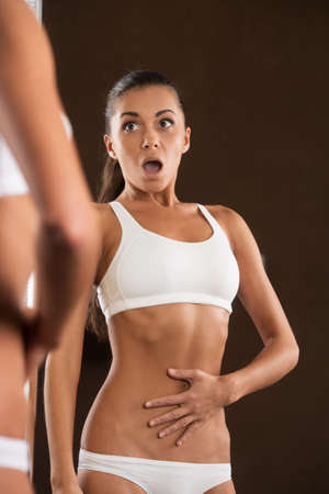 weight gain: scared young woman looking into mirror. beautiful girl standing without clothing in surprise Stock Photo
