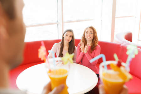 man carrying two glasses of juice. two girls sitting on sofa and clapping hands photo