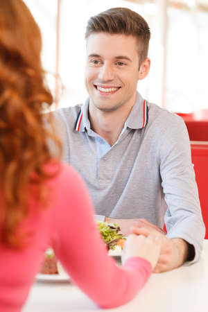 back of woman holding biyfriends hand at restaurant. mans and womans hands on table in cafe  photo