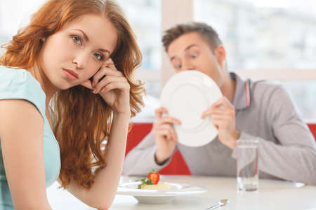 annoyed: man licking plate after finishing lunch. beautiful redhead girl turned away and waiting