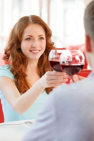 Young happy couple at romantic date. boy and girl drinking glass of red wine at restaurant photo