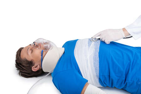 neck brace: doctor examining young patient on white background. young man lying with neck brace and mask