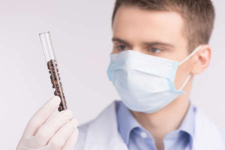 genetically modified: man holding provetta e indossare maschera. Colture cellulari test per testare i prodotti geneticamente modificati