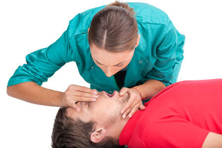 Young female giving patient CPR. man receiving artificial ventilation mouth to mouth