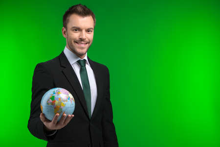 grip: Young businessman keeps world in his hand. Smiling man holding Earth on green background