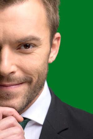 man face close up: Charming and handsome man half face close up. happy businessman standing on green background
