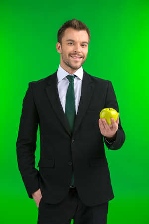 Businessman holding green apple in his hand. young guy standing on green background and smiling. photo