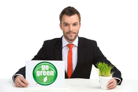 young caucasian man holding go green sign and grass. businessman with sign and grass sitting on white background photo