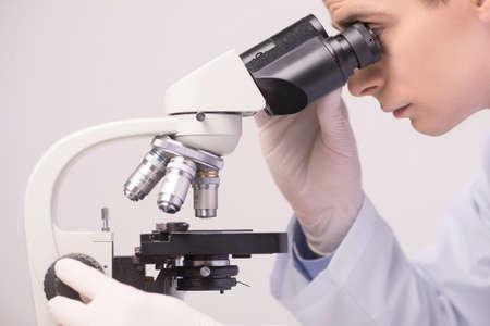 científico masculino para trabajar en ab con microscopio. elementos químicos que estudian en el laboratorio clínico Foto de archivo